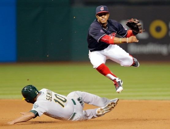 Cleveland Indians' Francisco Lindor, top, looks toward first base after getting Oakland Athletics' Marcus Semien out at second base in the eighth inning of a baseball game, Friday, July 10, 2015, in Cleveland. Billy Burns was out at first base for the double play. (AP Photo/Tony Dejak)